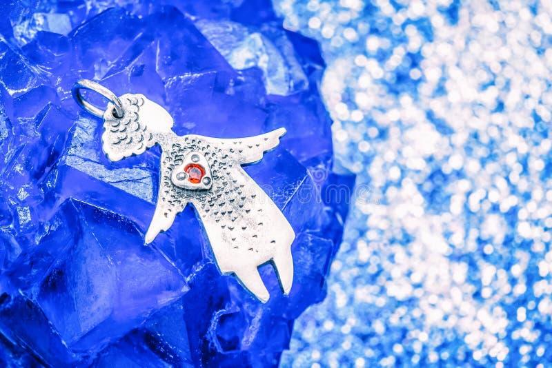 与一红心的银色下垂天使在一块蓝宝石 库存图片