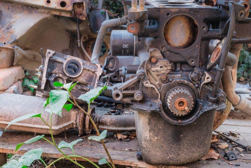 与一绿色植物的老生锈的引擎和汽车零件 图库摄影