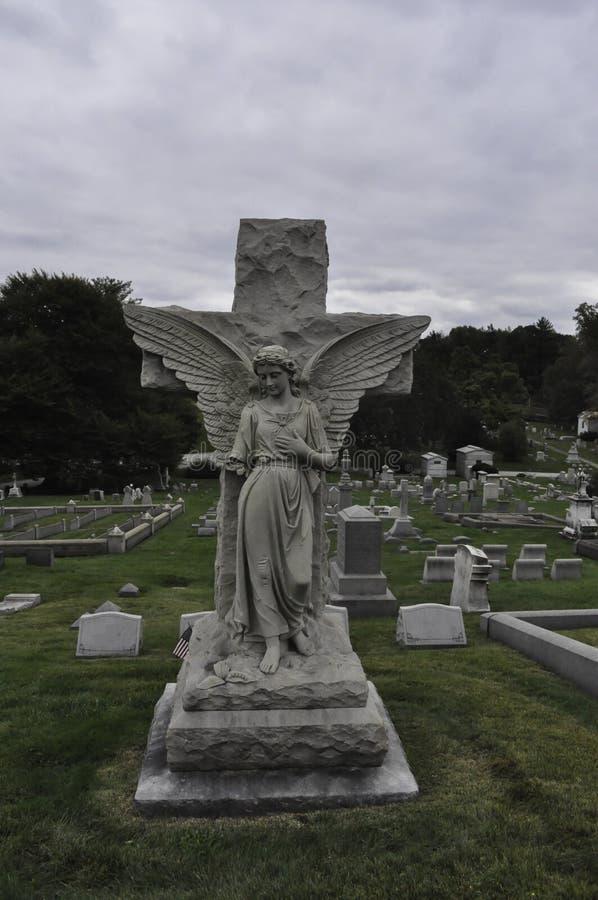 与一胳膊失踪和传播翼的损坏的天使雕象在看下来在公墓的十字架 库存图片