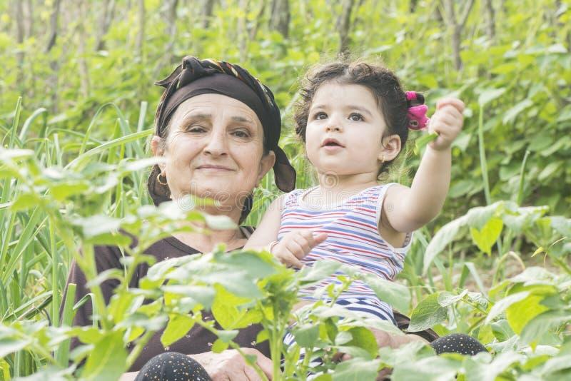 与一起享用她的孙的Grandmother先生画象庭院的 库存图片