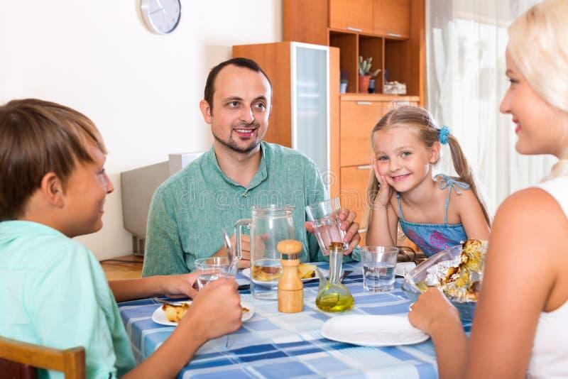 与一起用餐两个的孩子的愉快的家庭 库存照片