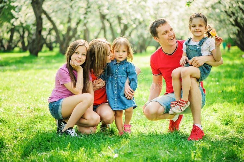 与一起花费时间的三个小女儿的大家庭在获得夏天公园、母亲、的父亲和的姐妹乐趣 免版税图库摄影