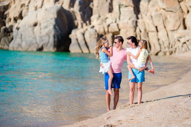 与一起走在热带海滩的孩子的愉快的美丽的家庭在暑假时 免版税库存图片