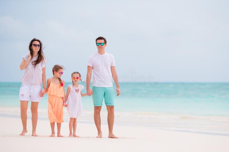 与一起走在热带海滩的孩子的愉快的美丽的家庭在暑假时 图库摄影