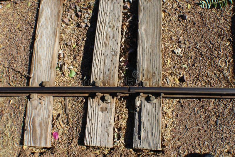 与一路轨的三条铁路领带风化了与螺栓 免版税库存图片
