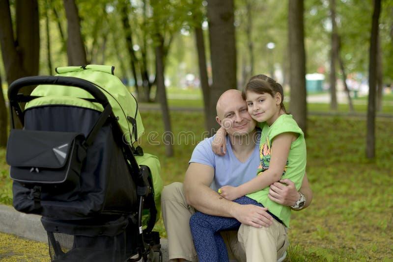 与一辆婴儿推车的父亲和女儿步行在森林公园在春天 库存图片