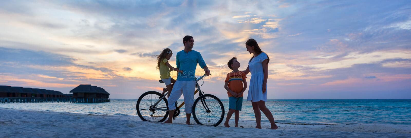 与一辆自行车的家庭在热带海滩 免版税库存照片