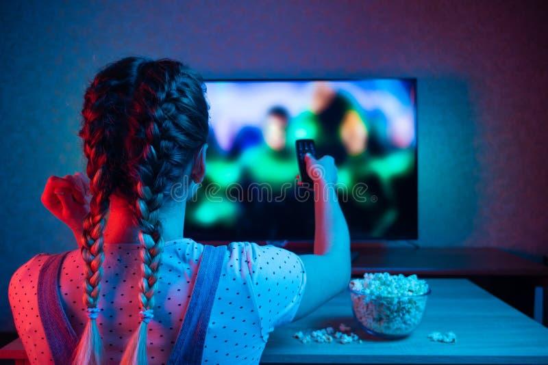与一遥控的少女电影与一碗在电视的背景的玉米花 光的一种明亮的颜色, 免版税库存照片