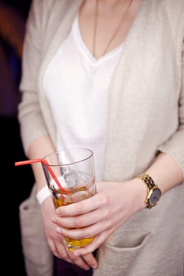 与一份饮料的玻璃在妇女的手上 免版税库存照片
