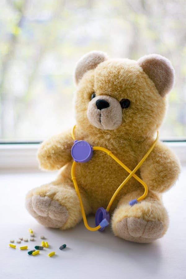 与一phonendoscope的逗人喜爱的玩具熊在小儿科医疗保健概念的药片旁边 库存图片