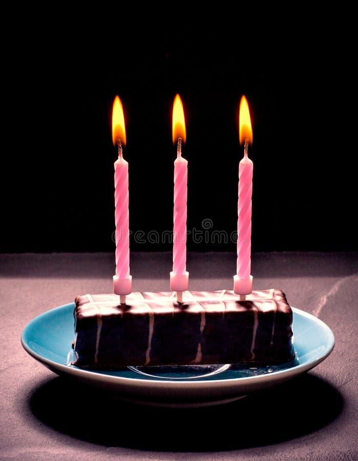 与三个桃红色蜡烛的巧克力蛋糕在蓝色板材 免版税库存照片