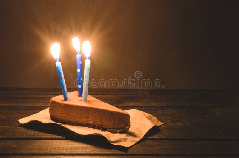 与三个燃烧的蓝色蜡烛的巧克力乳酪蛋糕在黑暗的背景 免版税库存照片