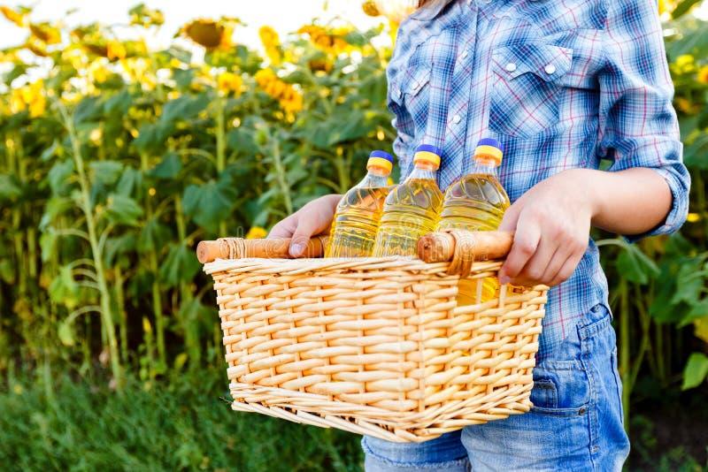 与三个瓶的篮子向日葵油在女孩的手上 免版税库存照片
