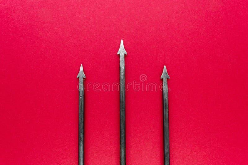 与三个钉的老,生锈和金属三叉戟在红色backgroun 免版税图库摄影