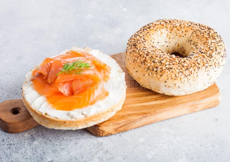 与三文鱼、乳清干酪和莳萝的新鲜的健康百吉卷三明治在轻的厨房用桌背景的葡萄酒砧板 健康二 库存照片