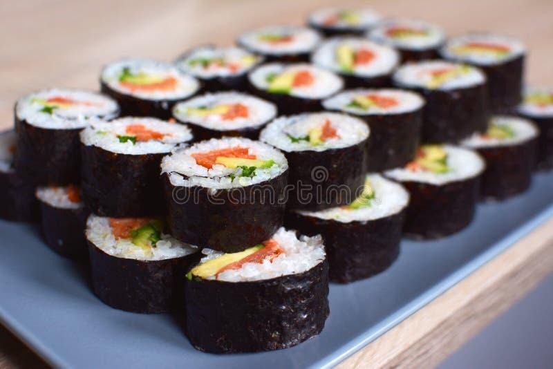与三文鱼、香葱和鲕梨的滚动的梅基寿司在一块灰色板材 图库摄影