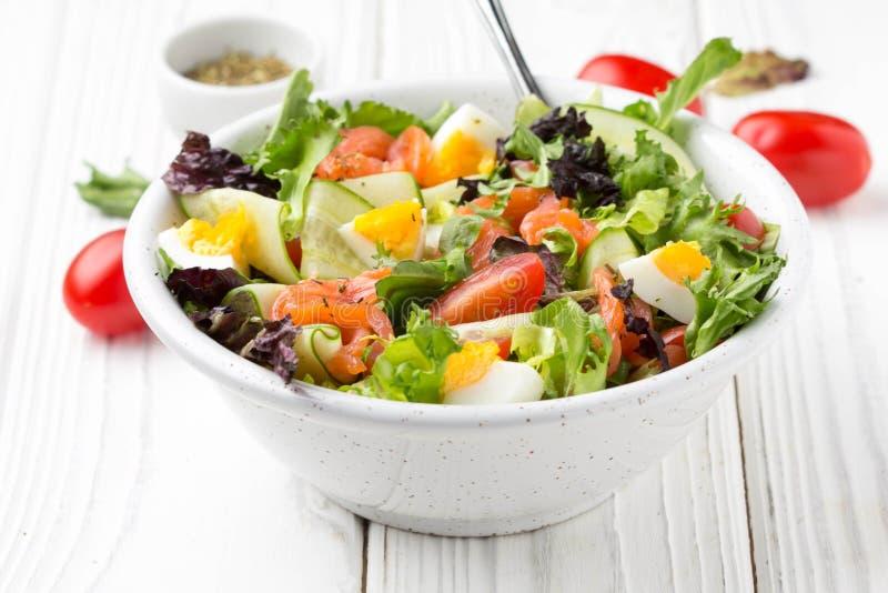 与三文鱼、鸡蛋和菜(西红柿、黄瓜,莴苣)的沙拉,可口便餐,健康食品 免版税库存照片