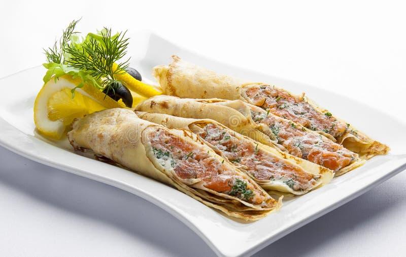 与三文鱼和奶油奶酪的薄煎饼在一块白色板材 库存图片