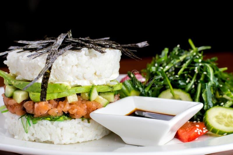 与三文鱼和沙拉的寿司汉堡与大豆souce 库存图片