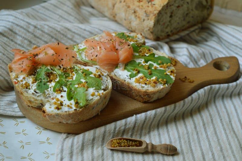 与三文鱼的两个三明治在木板 免版税图库摄影
