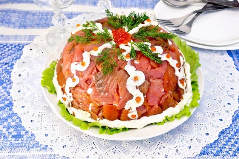 与三文鱼的沙拉在蓝色桌布的板材 免版税库存照片
