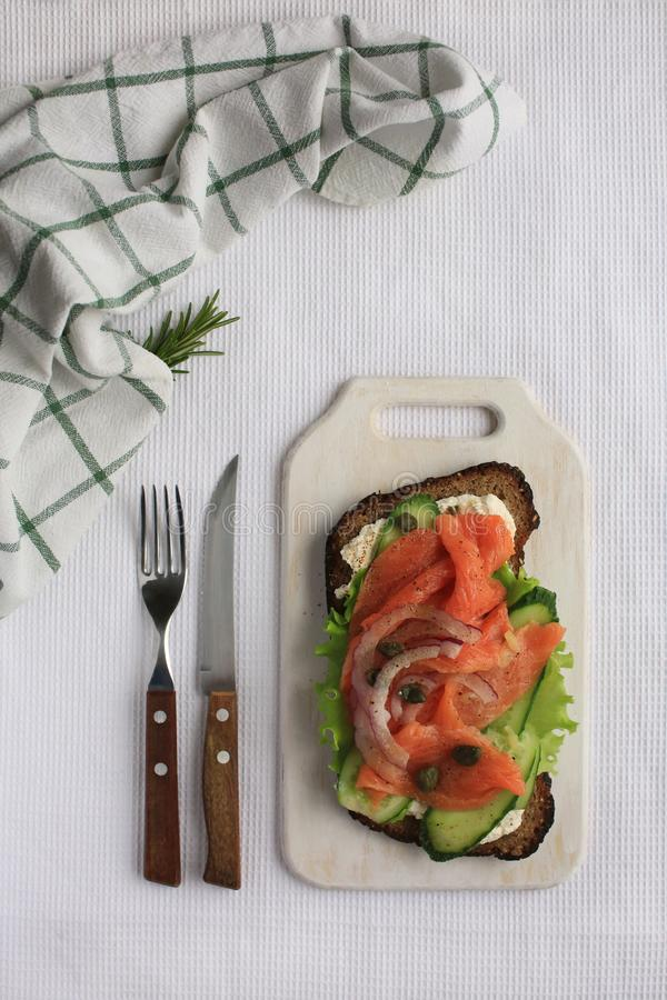 与三文鱼,绿色菜,在黑麦面包的白色乳酪的Smorrebrod 免版税库存图片