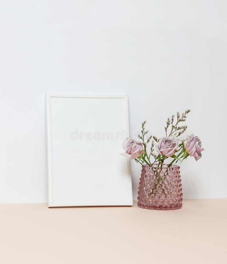 与三朵桃红色玫瑰的白色框架在书桌上 库存图片