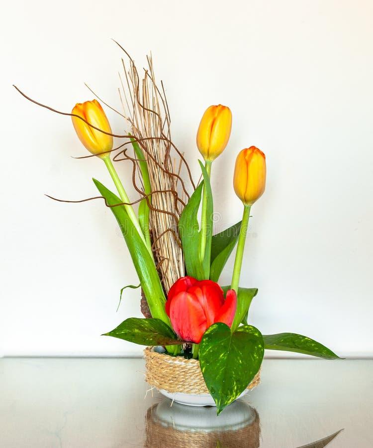 与三橙色郁金香和唯一红色郁金香的艺术性的花的布置 免版税库存图片