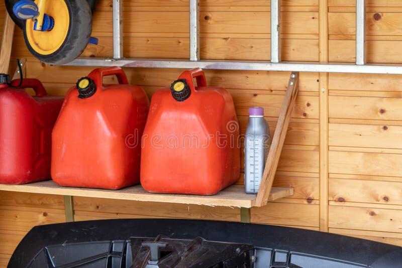 与三辆红色塑料燃料罐头、楼梯和除雪机的车库角落与木墙壁的atv的在背景 汽油气体 免版税图库摄影