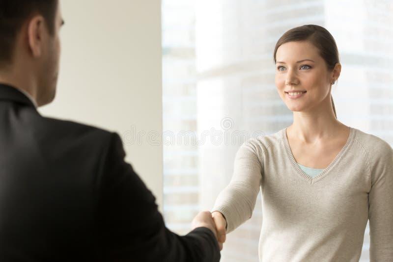 与上司的有吸引力的女性雇员握手 免版税库存照片