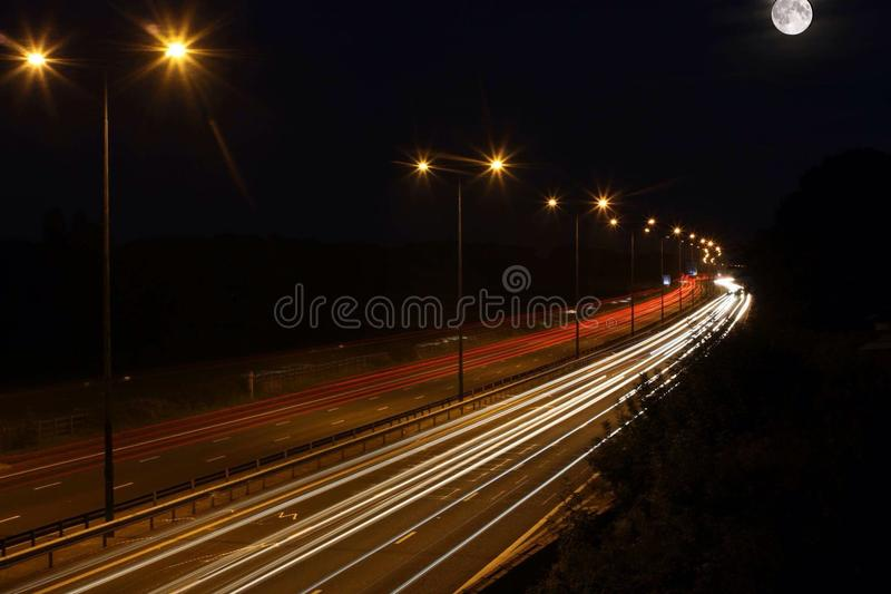 与上面月亮的长的曝光交通 库存照片