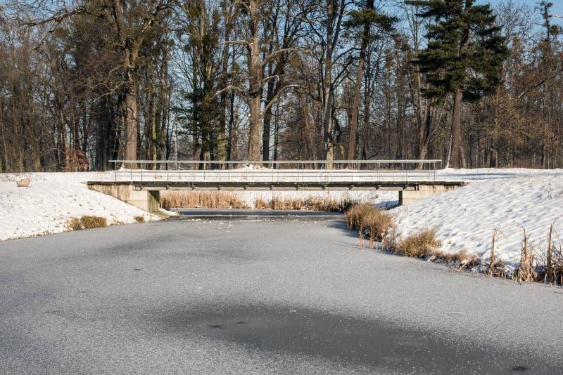 与上面桥梁的冻在背景的小河和树在捷克共和国的卡尔维纳市 免版税库存图片