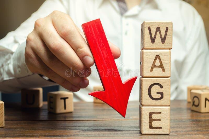 与下来词薪水和红色箭头的木块 薪金减少 在赢利的下落 危机绘制下降的财务费率 降职 低赢利 免版税库存照片