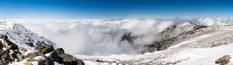 与下落的雪和白色云彩海的晴朗的冬日在足迹的对Mt圣安东尼奥(Mt鲍尔迪),洛杉矶县, 库存照片