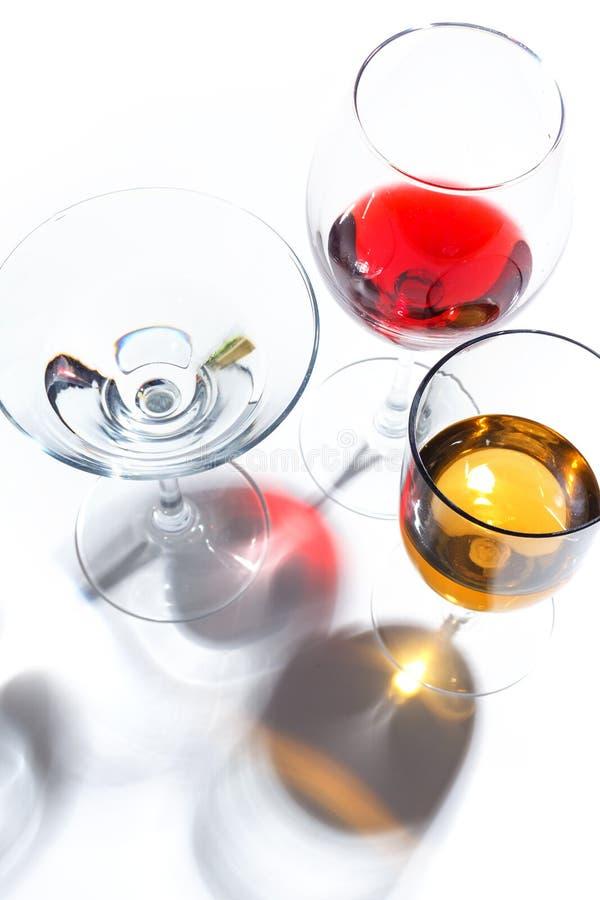 与不同颜色饮料的玻璃玻璃在白色背景的 顶视图 一个酒精鸡尾酒的概念 免版税库存照片