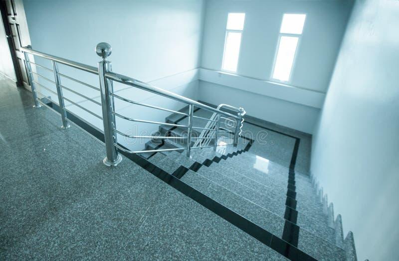 与不锈钢扶手栏杆的室内花岗岩楼梯 库存照片