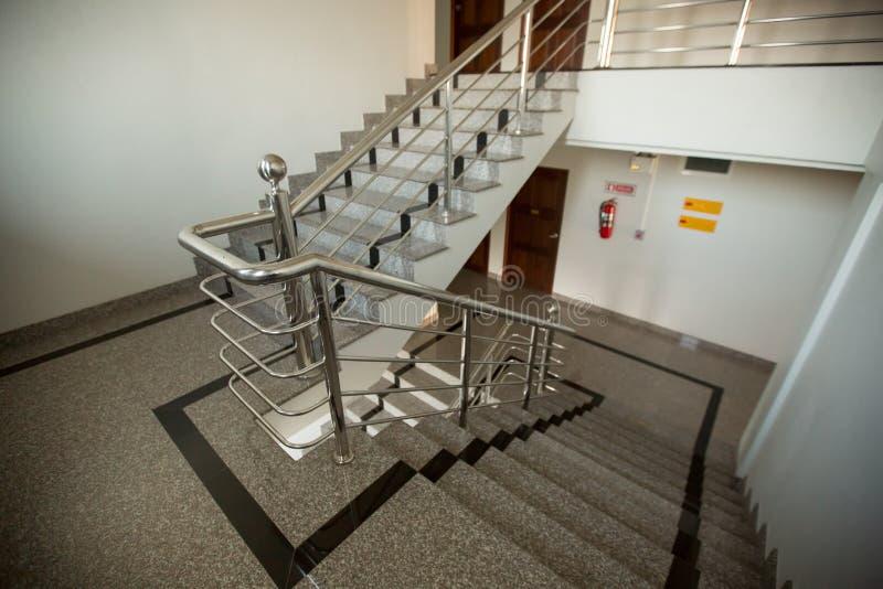与不锈钢扶手栏杆的室内花岗岩楼梯 库存图片