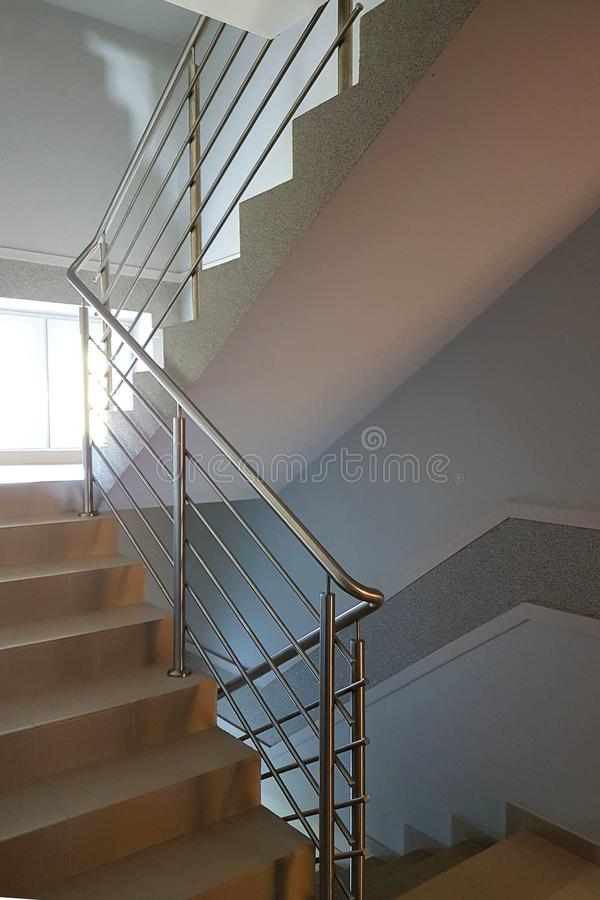 与不锈钢扶手栏杆的楼梯在一座现代高层建筑物 现代大厦内部  在上面的上升  免版税库存照片