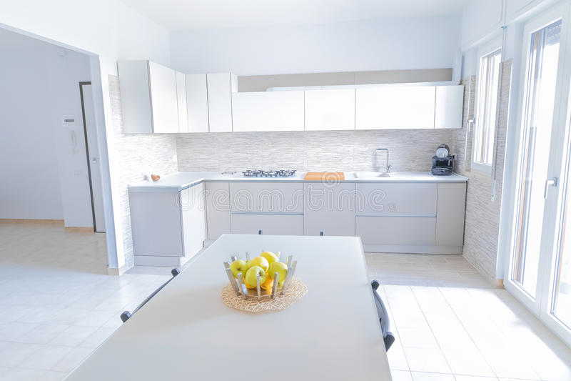 与不锈钢装置的现代,明亮,干净,厨房内部和在桌上的friut苹果在豪华房子里 免版税库存图片