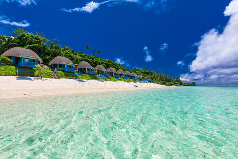 与与棕榈树和别墅,波里尼西亚的热带海滩 免版税库存照片