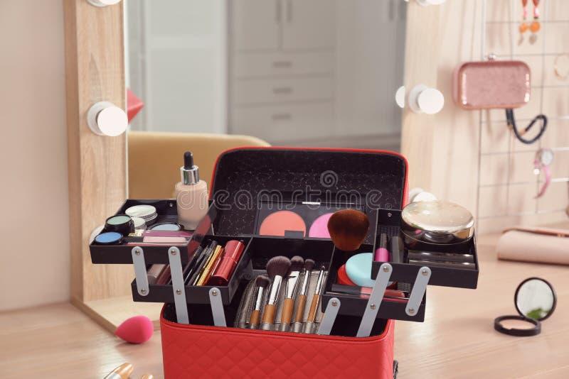 与专业构成产品和工具的美容师事例在木桌上 免版税库存图片