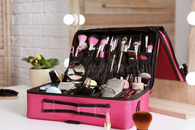与专业构成产品和工具的美容师事例在桌上 免版税库存照片
