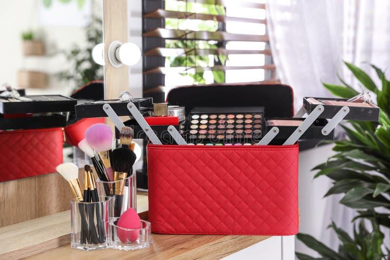 与专业构成产品和工具的美容师事例在梳妆台上 免版税库存照片