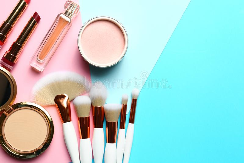 与专业构成刷子和不同的装饰化妆用品的平的被放置的构成在颜色背景 库存图片