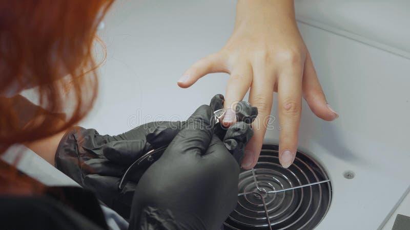 与专业钉子钳子的修指甲师清楚的表皮修指甲的 库存照片