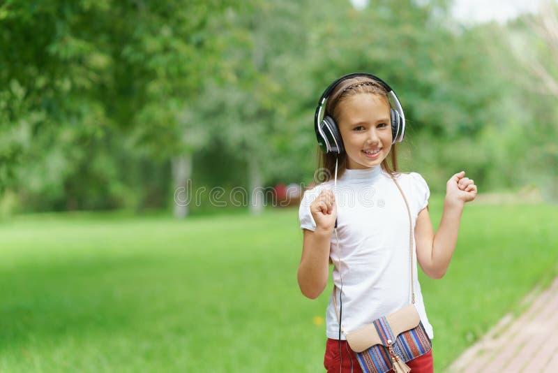 与专业DJ耳机的女孩听的音乐 免版税库存图片
