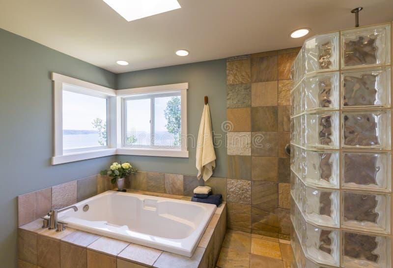 与丙烯酸酯的浸泡的木盆,大块玻璃阵雨、板岩瓦片墙壁和看法窗口的当代高级家庭温泉卫生间内部 库存照片