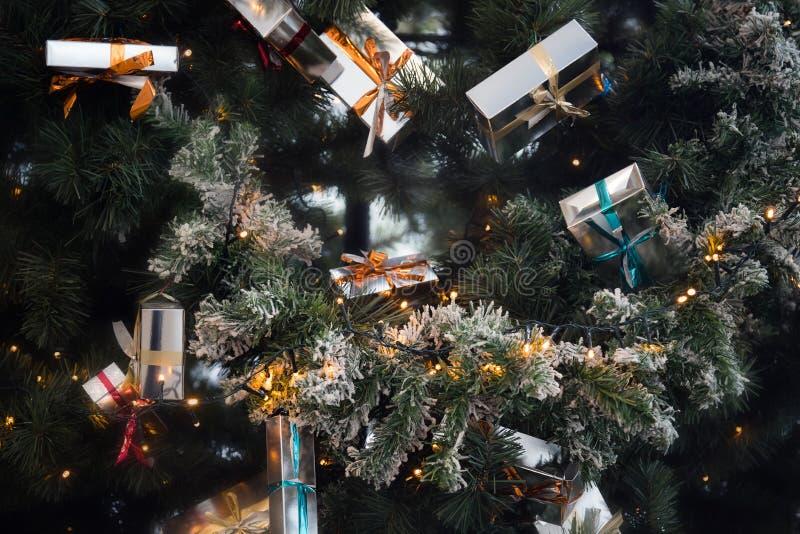 与丝带的圣诞礼物在垂悬在欢乐圣诞树的箱子 库存照片
