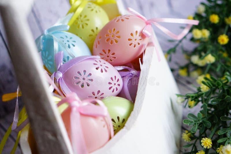 与丝带的色的鞋带复活节彩蛋在白色木篮子鞠躬 免版税库存照片