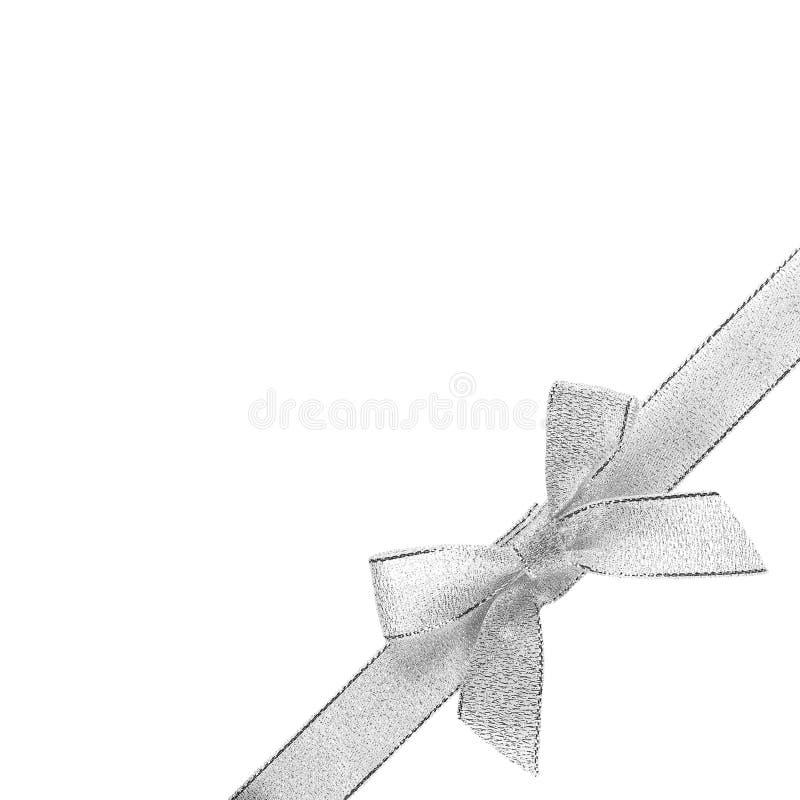 与丝带的银色弓在右下角 关闭 背景查出的白色 图库摄影